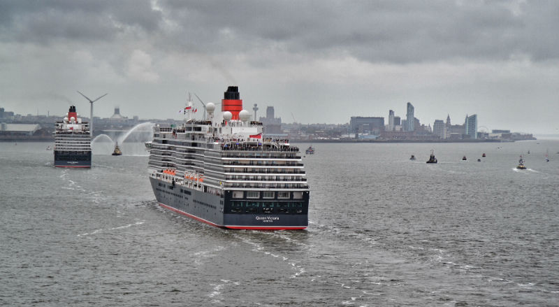 Cunard cruise liners Queen Victoria and Queen Elizabeth steam up the Mersey towards Liverpool's World Heritage waterfront, viewed from the flagship Queen Mary 2 bringing up the stern.