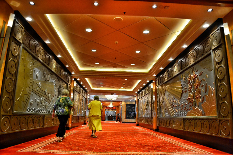 Wide, plush corridors on Deck 3 of Cunard's Queen Mary 2 - red carpets, recessed ceiling lighting and large bas-reliefs on the walls depicting the seasons Winter and Summer