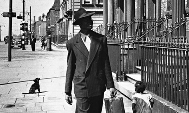 An immaculately attired West Indian man looks for accommodation among the tall townhouses in Liverpool's Parliament Street, 1949
