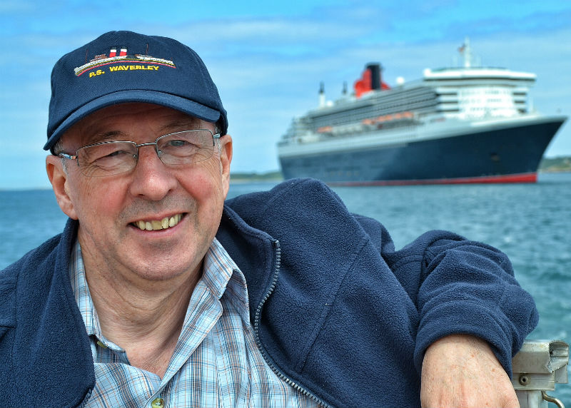 Maritime author Peter Elson aboard a St. Peter Port tender with Cunard's flagship Queen Mary 2 moored in the background